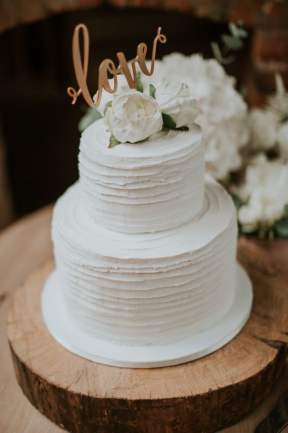 a white textural wedding cake with stripes, white blooms and a gold calligraphy topper