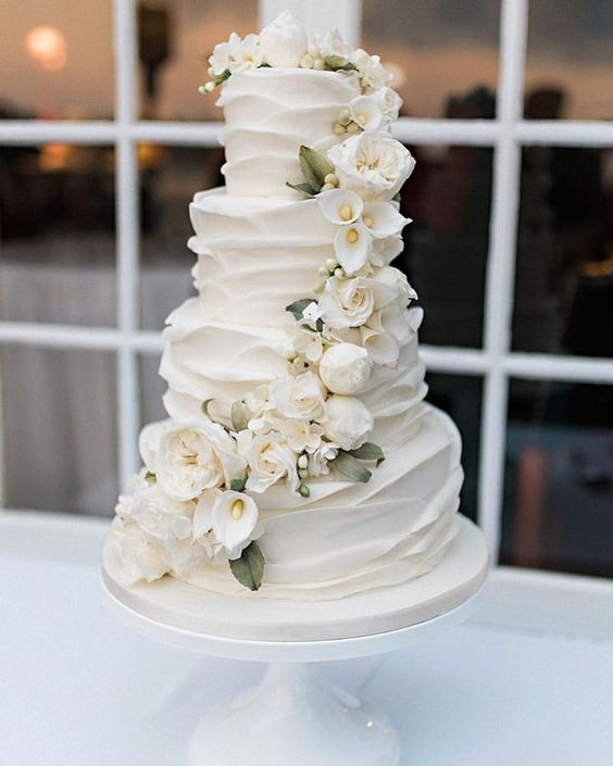 a white textural wedding cake with white blooms and leaves is a refined and chic idea