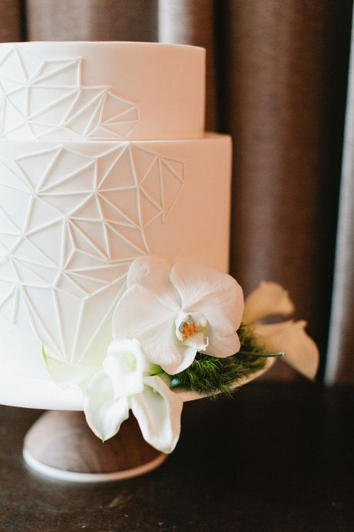 a white wedding cake with geometric patterns, white orchids and greenery is very elegant