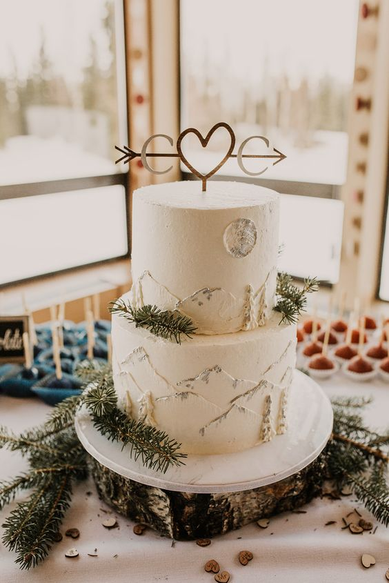 a white wedding cake with mountains painted, a cute topper and some fir branches is very lovely