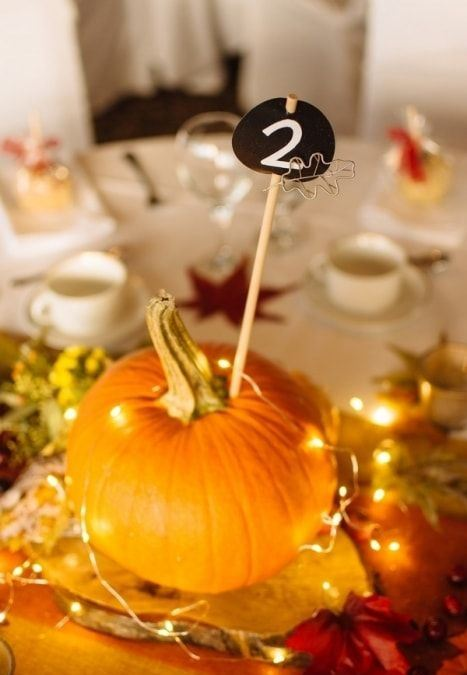 a wood slice, a pumpkin, lights and a chalkboard table number for wedding tablescape styling