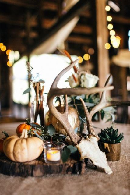 a woodland fall wedding centerpiece of a wood slice, pumpkins, eucalyptus, antlers and a succulent in a pot