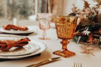 amber and pink goblets, gold cutlery, copper napkins and bright dried leaves are great for a fall wedding