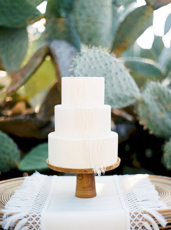 an all white wedding cake decorated with macrame is great for desert or boho weddings