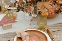an earthy-colored fall wedding tablescape with neutral linens, woodne plates, a bright floral centerpiece and pink wedding stationery