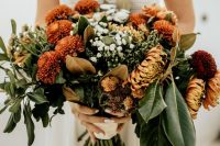 an earthy-tone fall wedding bouquet of orange, rust and white blooms, greenery and foliage is a stunning idea for the fall