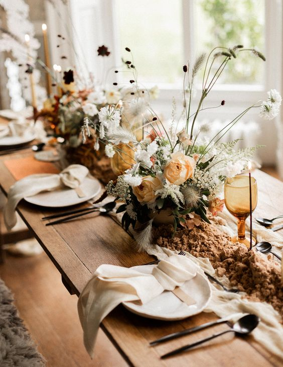 an earthy-toned wedding tablescape with neutral linens, white and pastel blooms with twigs and amber glasses is a delicate idea for the fall