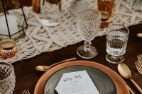 an elegant boho wedding tablescape with terracotta plates, amber glasses and candleholders, a macrame runner and candle lanterns