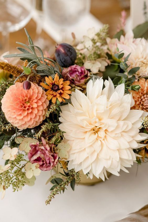 an elegant fall wedding centerpiece of pink, rust, orange and creamy blooms, greenery and figs