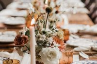 an elegant fall wedding tablescape spruced up with amber glasses and cutlery, rust and amber blooms