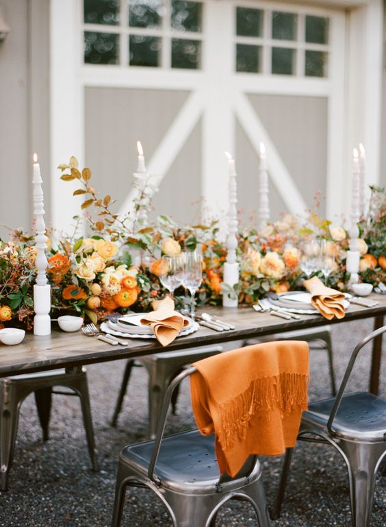 an elegant orange wedding tablescape with a super lush floral table runner, lovely tall candles and orange blankets for cuddling