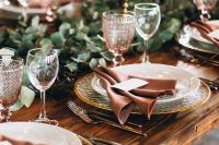 an elegant rustic fall tablescape with a greenery runner, tall candles in gold candlesticks, hammered chargers, pink glasses and dusty pink napkins