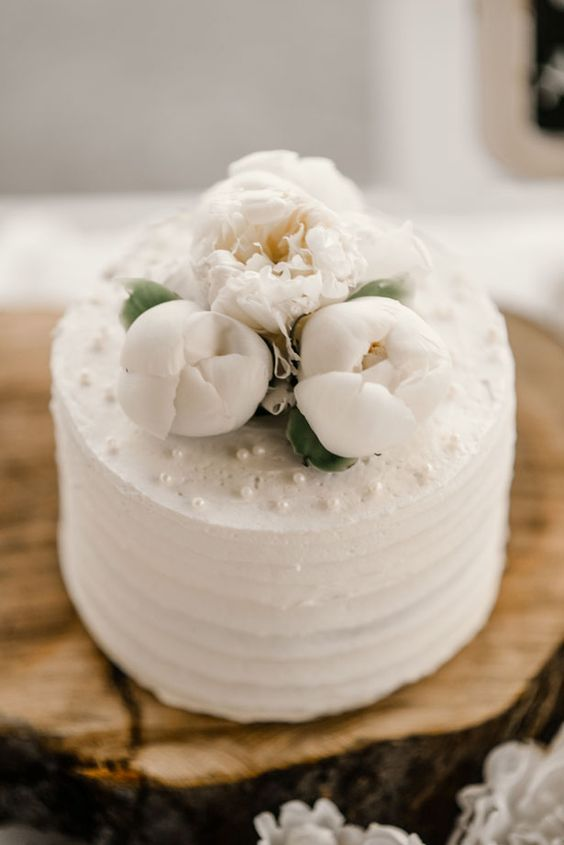 an elegant textural white wedding cake topped with white peonies and edible pearls will never go out of style