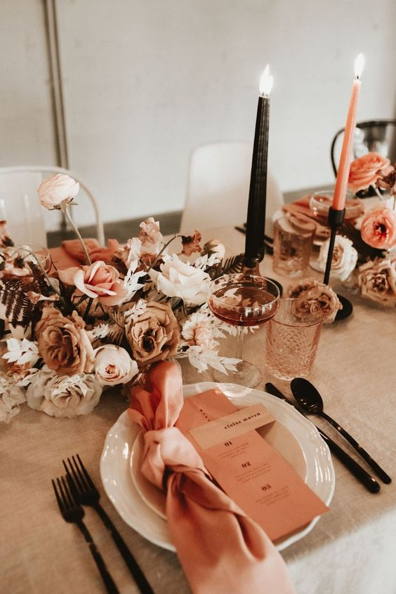 an elegant warm-colored fall wedding tablescape with a neutral tablecloth and pink apkins, earthy-toned floral centerpieces, black and rust candles