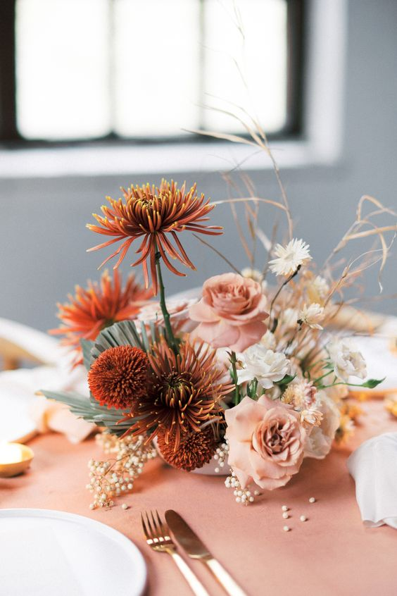 an ethereal wedding centerpiece with white, blush and rust-colored blooms and dried herbs for a fall wedding