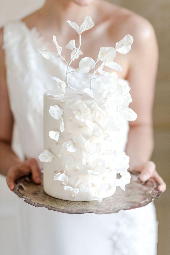 an ethereal white wedding cake decorated with beads and pearls plus white sugar leaves and petals is amazing