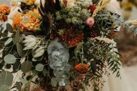 an incredibly lush fall wedding bouquet of orange, rust, pink, deep purple and yellow blooms, lots of various greenery, wheat and berries