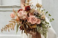 an organic super dimensional pastel wedding bouquet with blush and rust blooms, gold and green leaves and some herbs for a delicate feel
