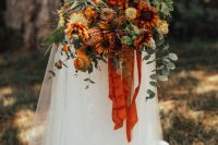 an out of the box fall wedding bouquet of orange, rust and burgundy blooms, greenery, berries and air plants plus orange ribbons is a stunning idea