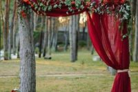 an outdoor fall wedding altar with a red curtain, greenery and bold blooms plus a candle lantern with red candles