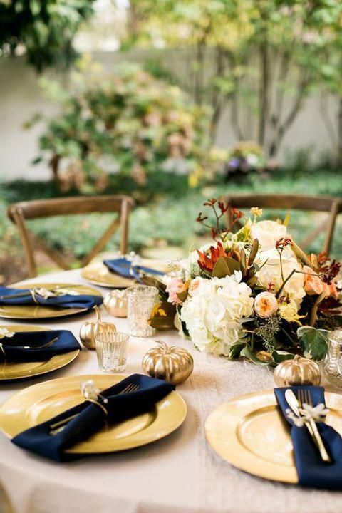 an outdoor fall wedding table with a lush floral centerpiece, gold chargers, navy napkins with gold cutlery and gold pumpkins for decor