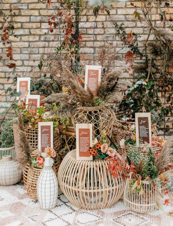 beautiful outdoor fall wedding decor with rattan tables and ottomans, fall foliage and blooms, pampas grass and signage