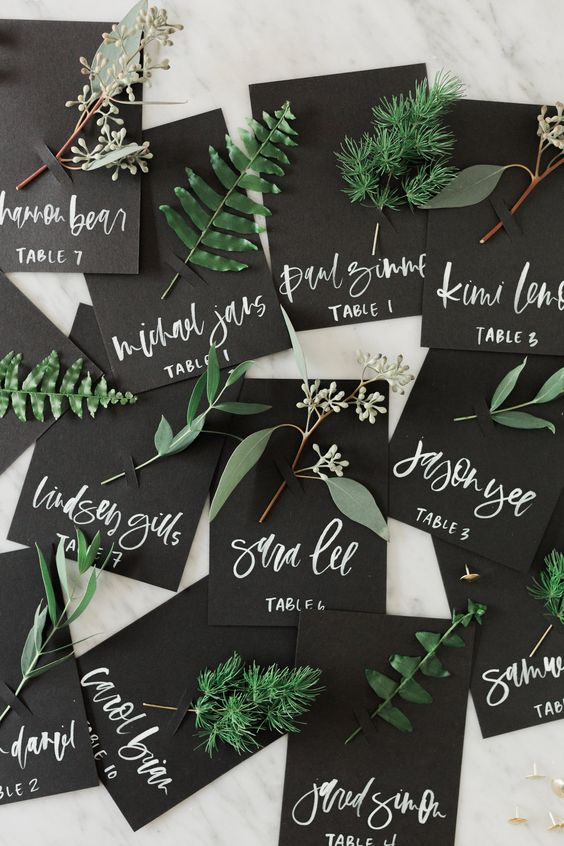 black cards with names and fresh greenery attached are very natural escort cards for a fall or other wedding