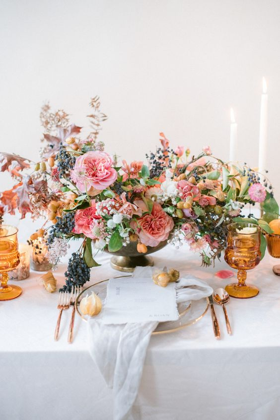 copper cutlery, amber goblets and a lush floral and berry centerpiece make the tablescape very chic and refined