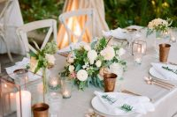 copper glasses and cutlery, copper candle lanterns and neutral blooms create a chic tablescape