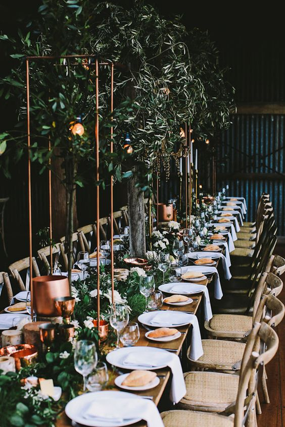 copper goblets, tall copper centerpieces and copper candleholders, greenery and neutral linens