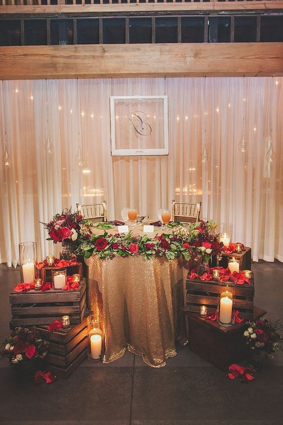deep red petals and blooms accent the rustic glam sweetheart table and add a touch of bold color