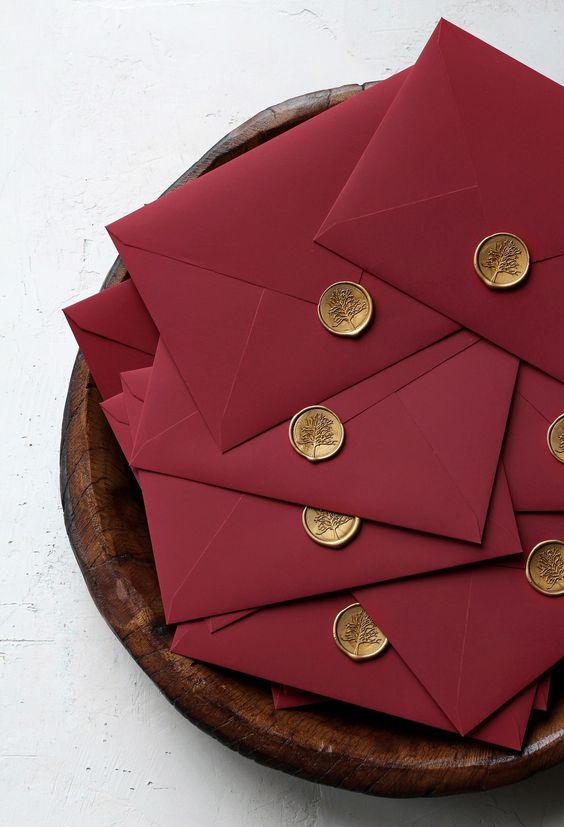 elegant burgundy envelopes with gold seals are amazing for a bold fall or winter wedding
