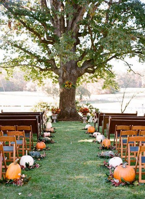 fall leaves and pumpkins to line up the aisle and bold fall blooms to accent the ceremony space
