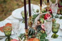 green leaves, pumpkins, pomegranates, antlers and dark candles for a woodland-inspired tablescape