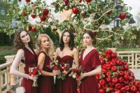 mismatching deep red bridesmaid maxi dresses and a stack of red apples for wedding decor
