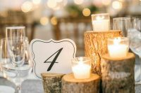 tree stumps and branches with candles and a cutout table number for a simple fall or winter rustic centerpiece