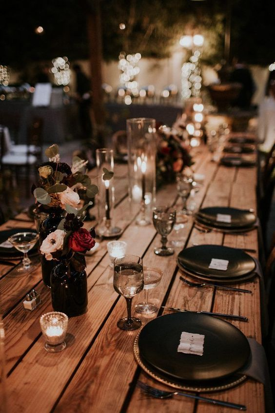 a Halloween wedding table with black plates and cutlery, black candles, deep purple, red and blush blooms