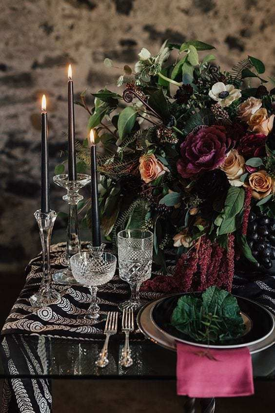 a beautiful decadent Halloween wedding table with a printed runner, fuchsia napkins and a lush centerpiece with matching blooms, black candles