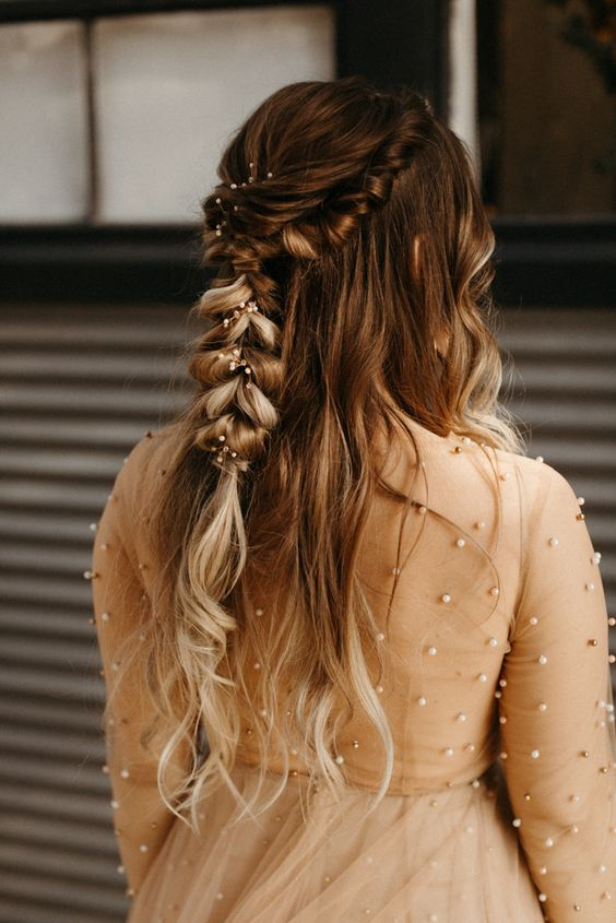 a beautiful wedding half updo with a twisted loose braid and waves down, with fresh blooms tucked in is a gorgeous idea for a romantic bride