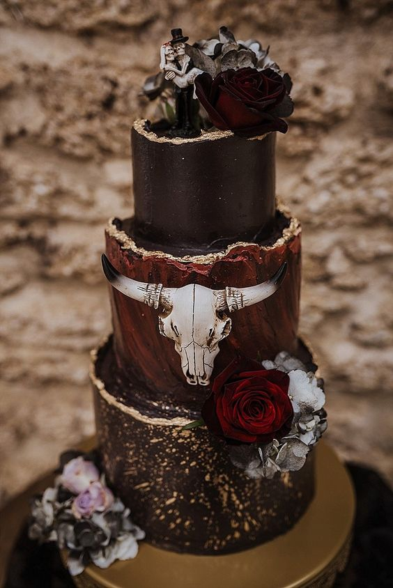 a black and burgundy wedding cake with a gold edge, a skull, blooms and skeleton toppers for Halloween