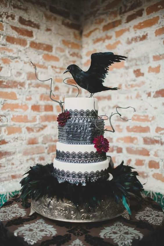 a black lace and white wedding cake with twigs, burgundy blooms and a faux blackbird on top is ideal for Halloween