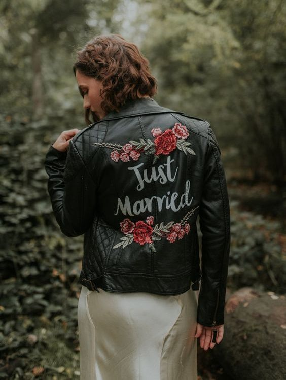 a black leather jacket with colorful floral handpainting is a trendy fall coverup idea to rock