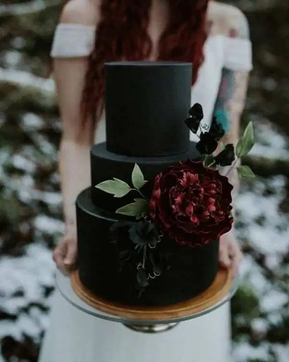 a black matte wedding cake decorated with sugar blooms and leaves is a stylish idea for Halloween