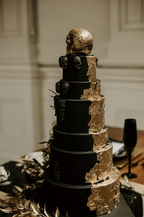 a black matte wedding cake with gold leaf, sugar skulls and a large gold skull ont op is very chic