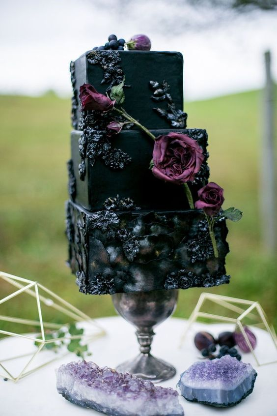 a black square wedding cake with sugar blooms, purple blooms, figs and berries is a stylish Halloween idea