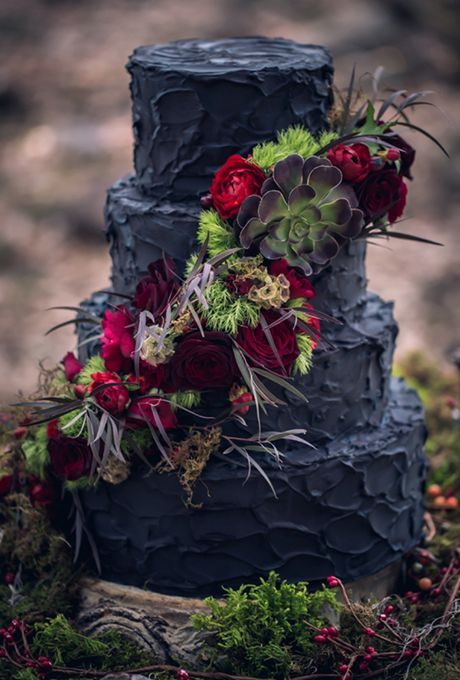a black textural buttercream wedding cake with bright blooms, moss, a large succulent and foliage for Halloween