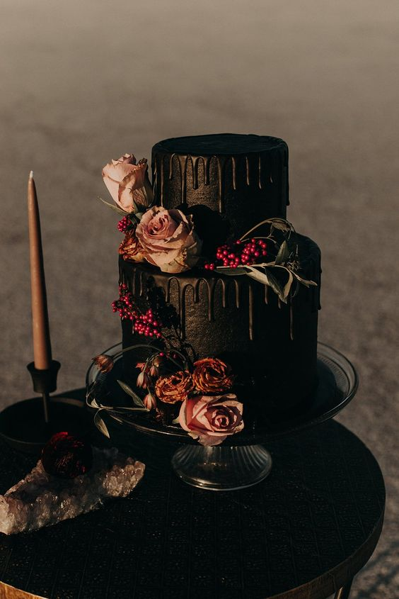 a black wedding cake with black drip, pastel blooms, leaves and berries for a Halloween wedding