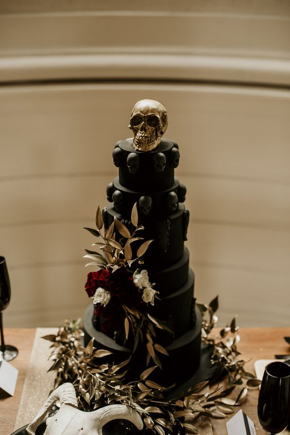 a black wedding cake with black skulls, burgundy and white blooms and gilded leaves plus a gold skull on top
