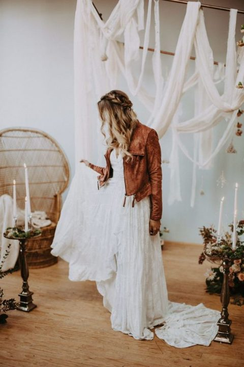 a boho bride in a lace dress and a brown leather jacket with tassels that adds color to the look