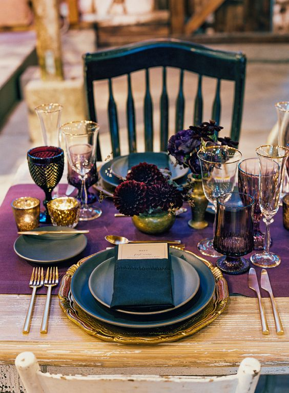 a breathtaking Halloween wedding table with a purple runner, deep purple and burgundy blooms, gold cutlery, placemats and candleholders